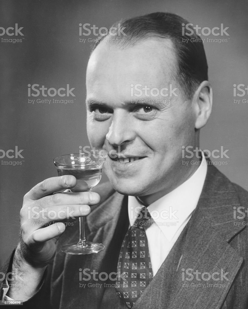 Man in full suit raising  glass of wine,  (B&W), close-up, portrait stock photo