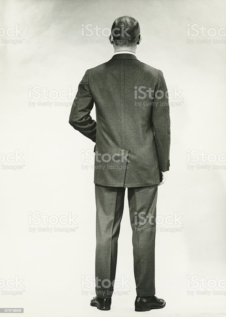 Man in full suit standing in studio, (Rear view), (B&W) stock photo