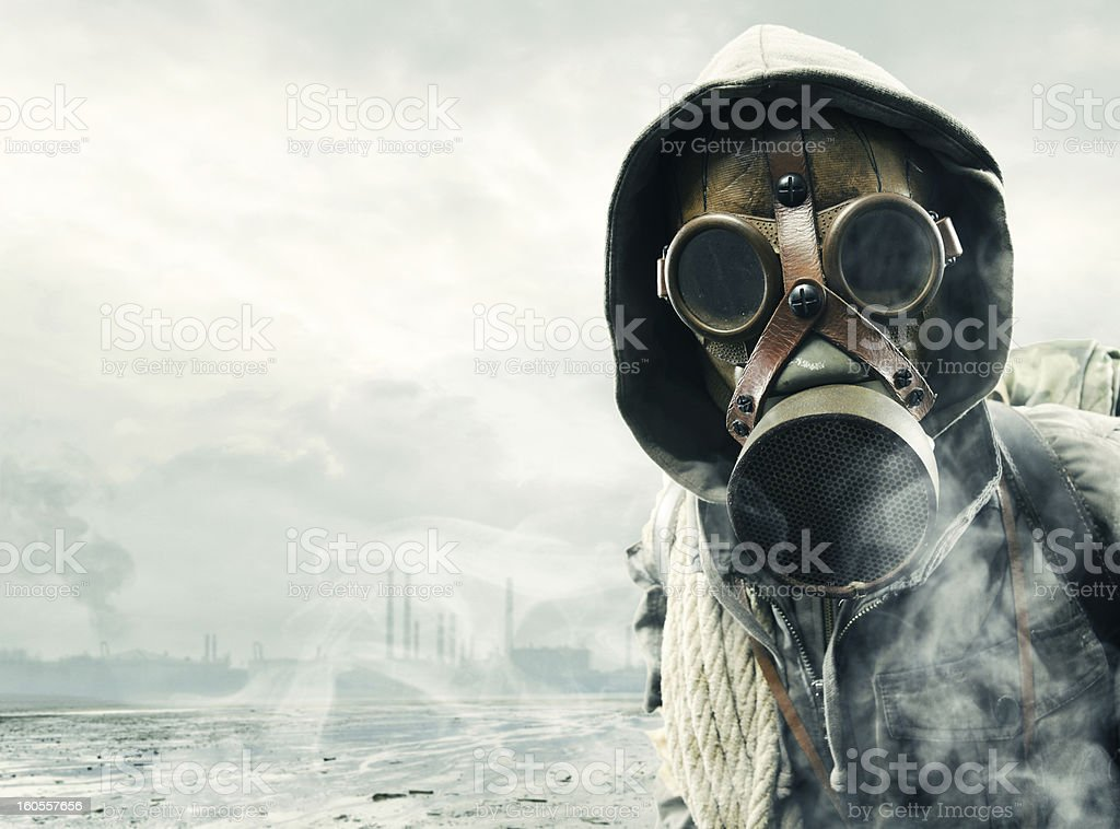 Man in gas mask witnessing environmental disaster stock photo
