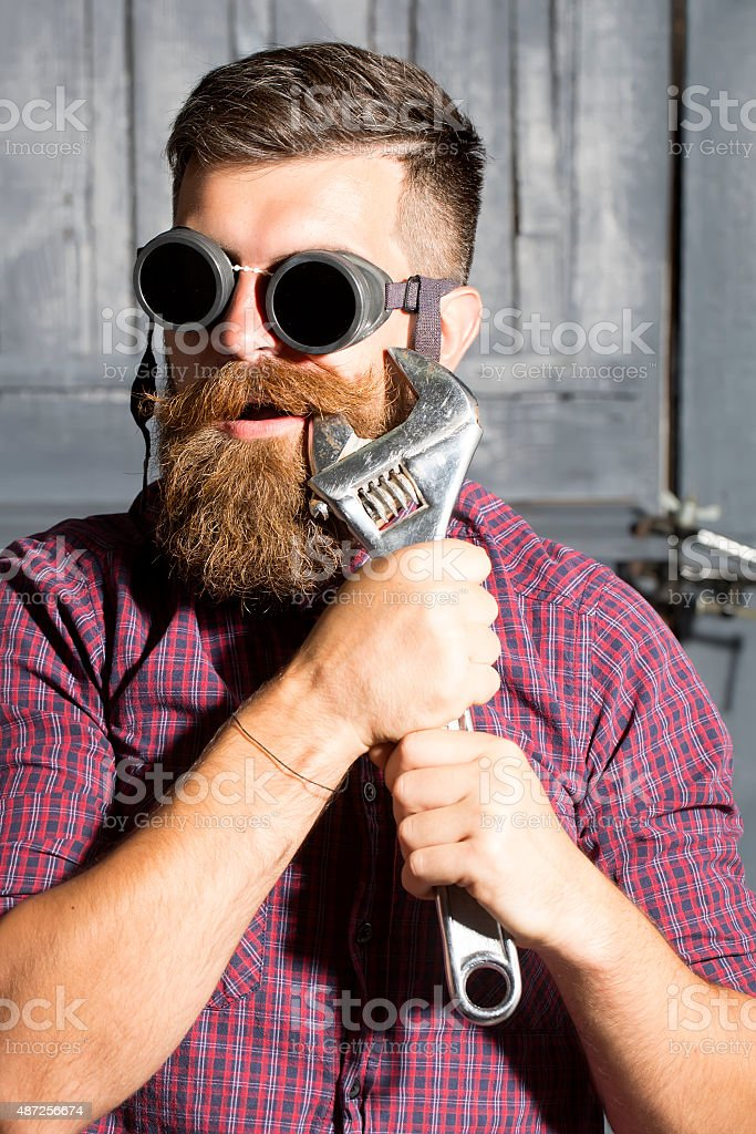 Man in glasses standing with spanner stock photo