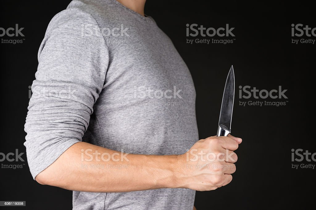 man in gray shirt holding knife stock photo