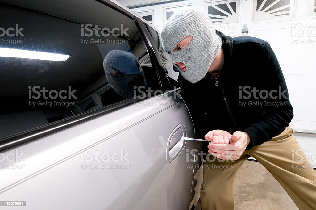 Man in gray ski mask attempting to break into vehicle royalty-free stock photo