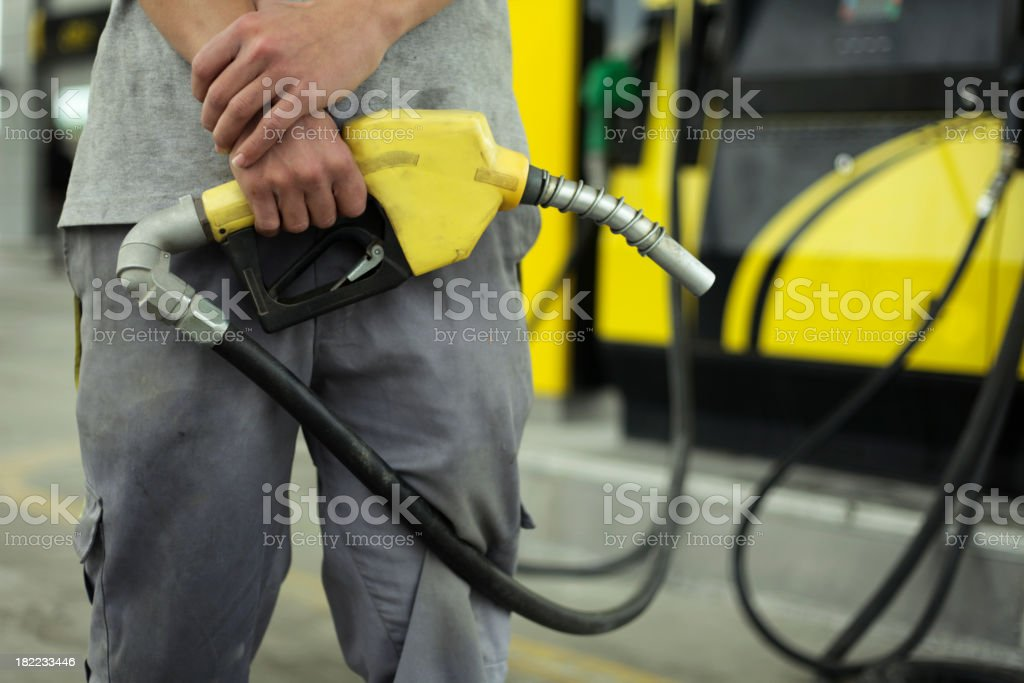 Man in gray standing at gas station holding yellow pump stock photo