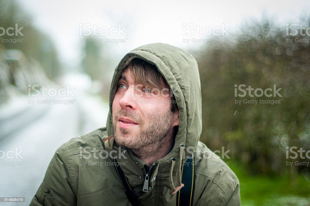 Man in Green coat looking to the side stock photo