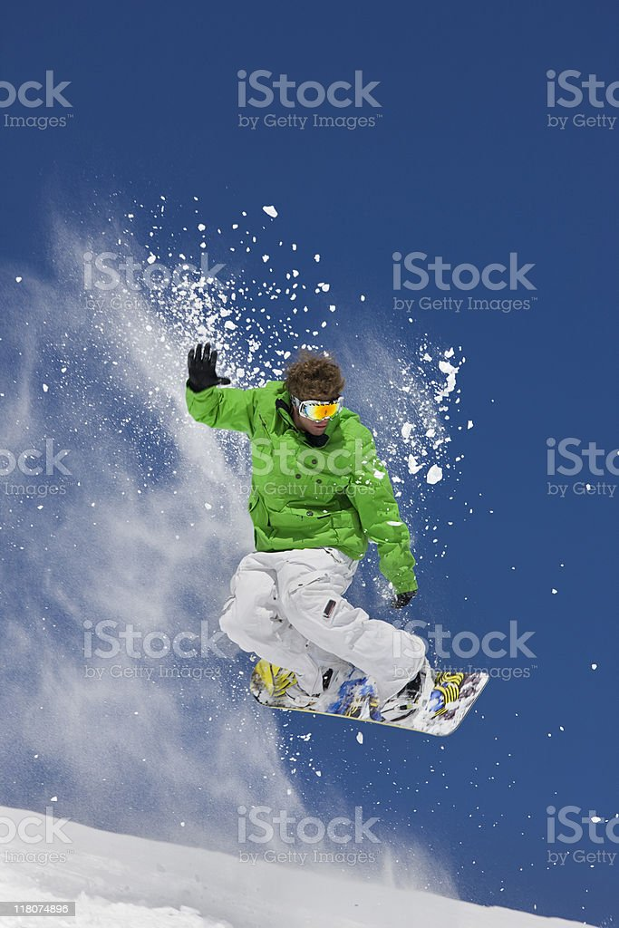 Man in green jacket extreme jumping on a snowboard royalty-free stock photo
