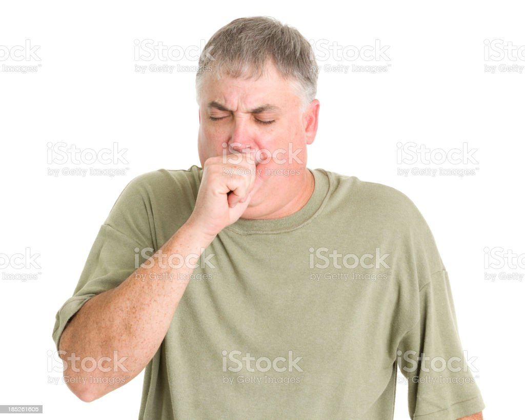 Man in green shirt coughing into his fist stock photo
