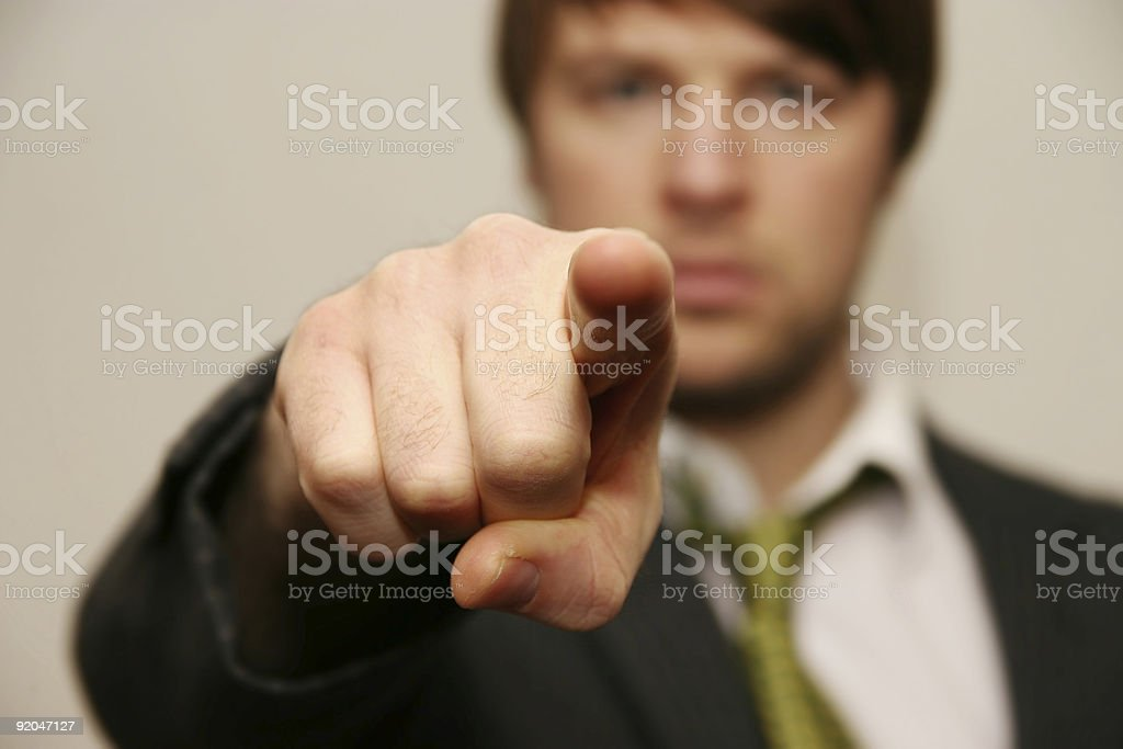 A man in green tie with his arm out pointing at you stock photo