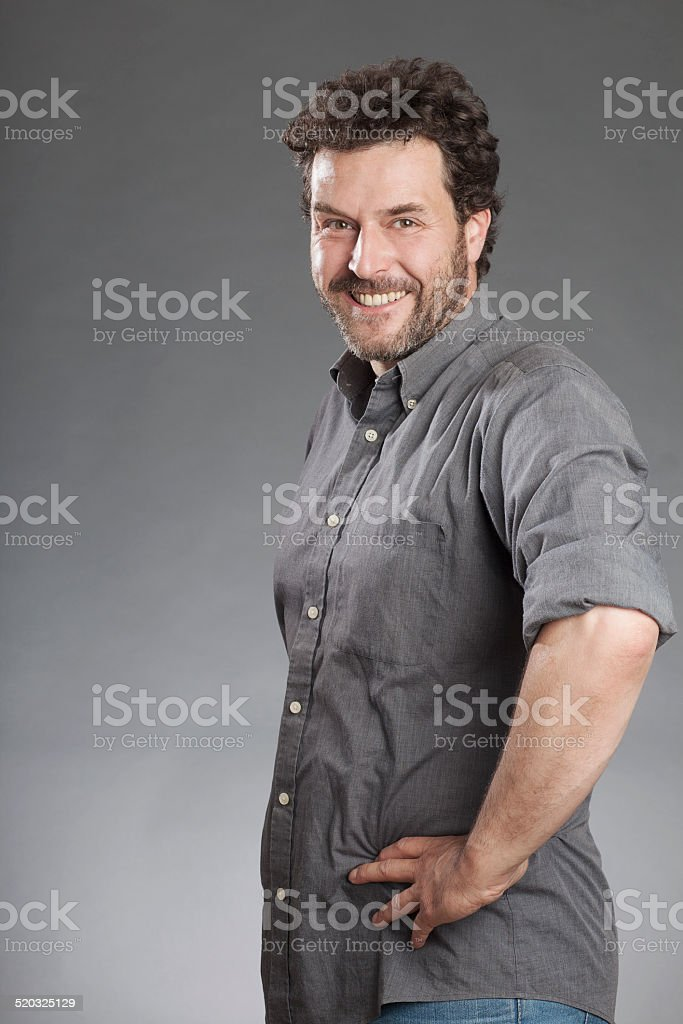Man in grey shirt standing with hands on hips stock photo