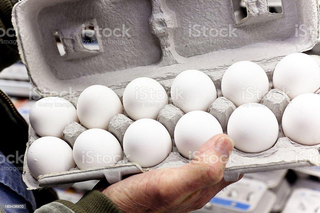 Man in grocery store inspecting carton of a dozen eggs. stock photo