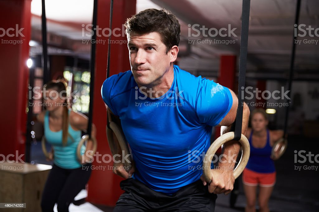 Man In Gym Exercising With Gymnastic Rings stock photo