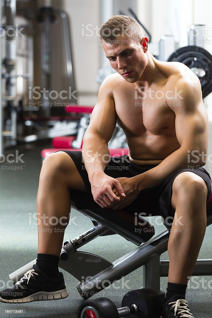 Man in gym or fitness studio on weight bench royalty-free stock photo