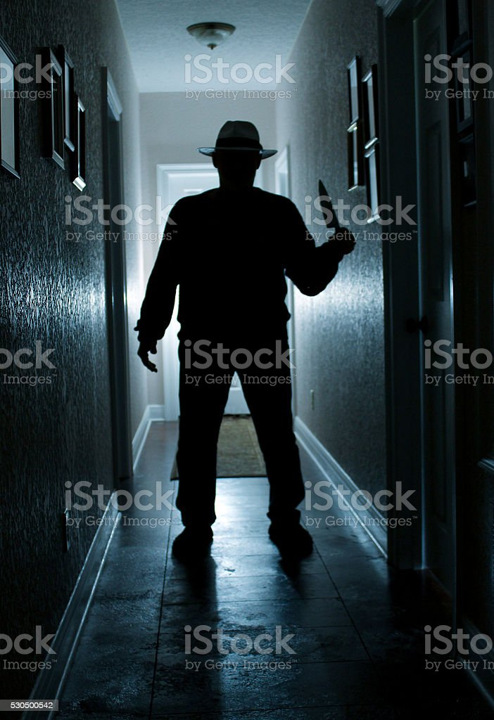 Man in Hall With Knife stock photo