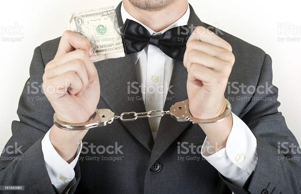 Man in handcuffs for business crime with dollar stock photo