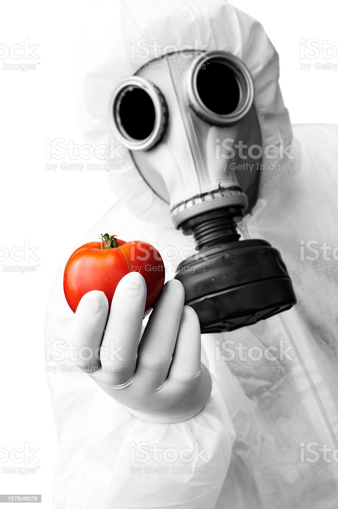 Man in hazmat suit holding a tomato stock photo