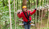 Man in high rope course climbing for sport