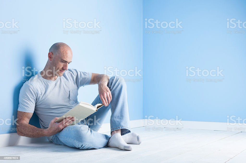 Man In His 30s Stting On The Floor Reading stock photo