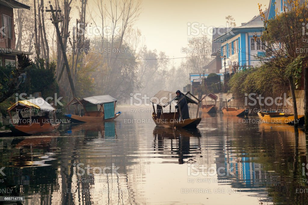 A man in his shikara boat rowing in backwater of Dal Lake stock photo