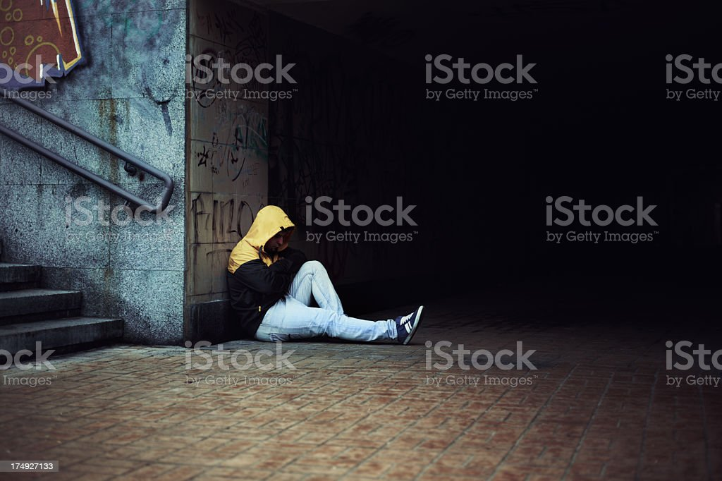 Man in hooded shirt and jeans sitting on underground floor royalty-free stock photo