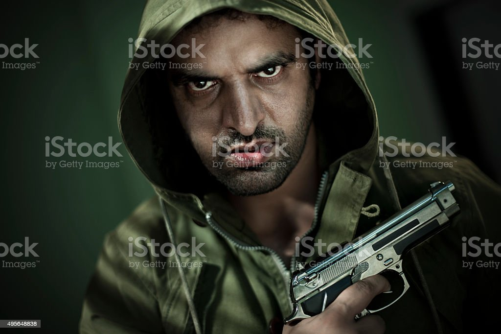 Man in hoodie jacket with a gun and sharp gaze. stock photo
