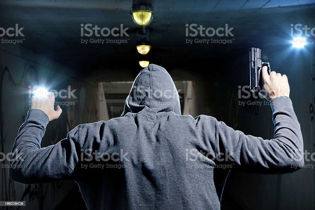 Man in hoodie with gun surrendering with arms up stock photo