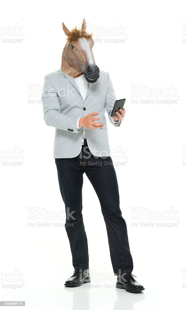 Man in horse costume and using phone stock photo
