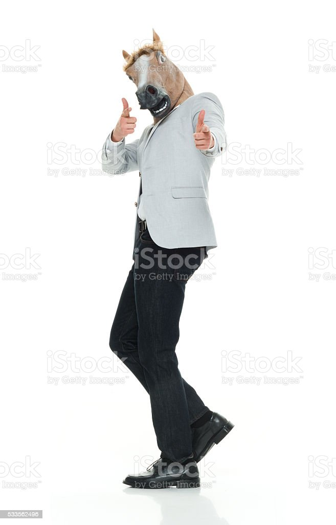 Man in horse face mask giving thumbs up stock photo