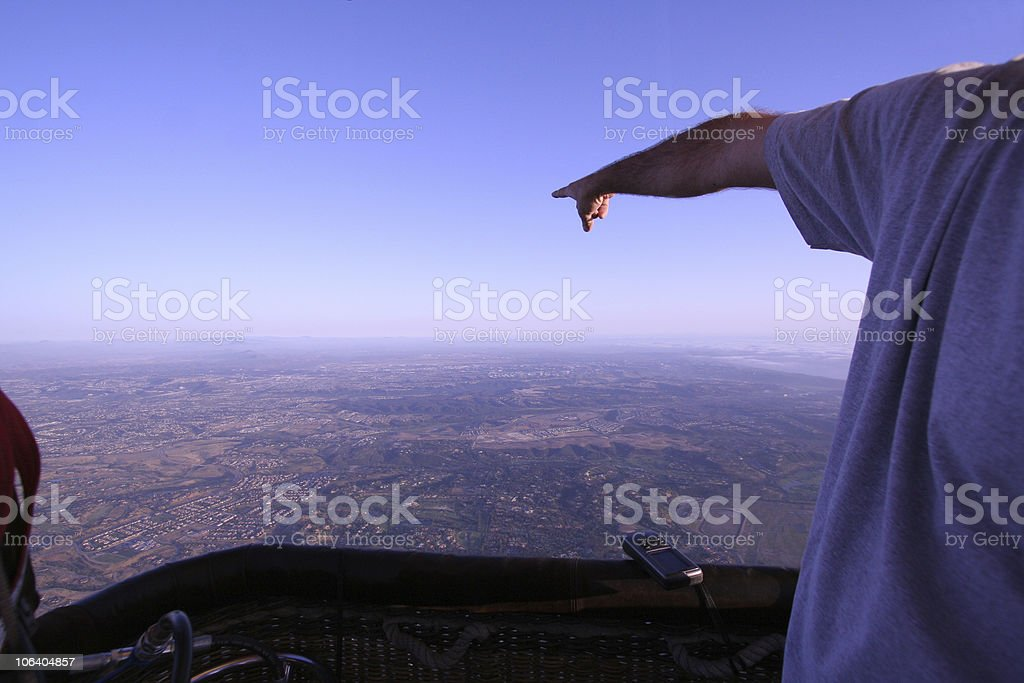 Man in hot air balloon pointing into space royalty-free stock photo