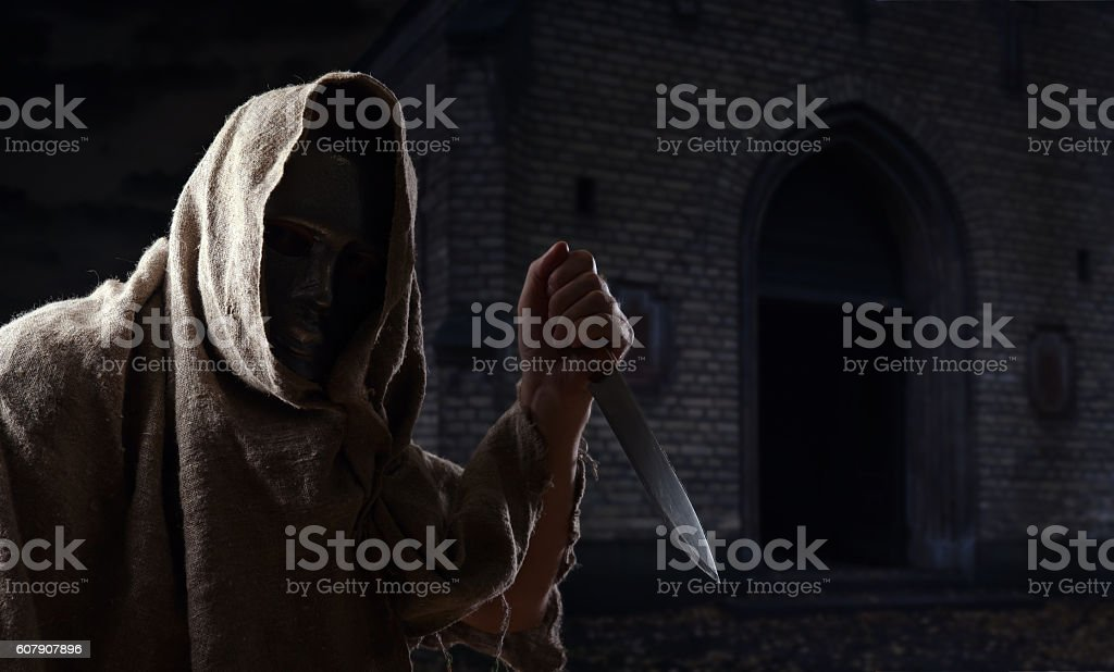 man in iron mask with knife stock photo