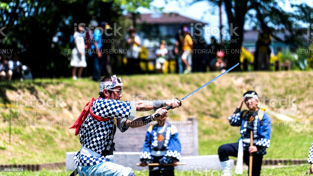 Man in Japanese traditional clothing hold a katana sword for performance stock photo
