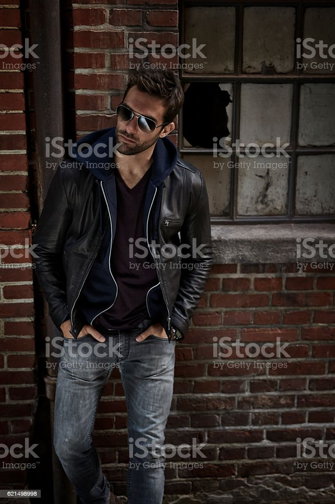 Man in jeans and leather jacket, looking away stock photo