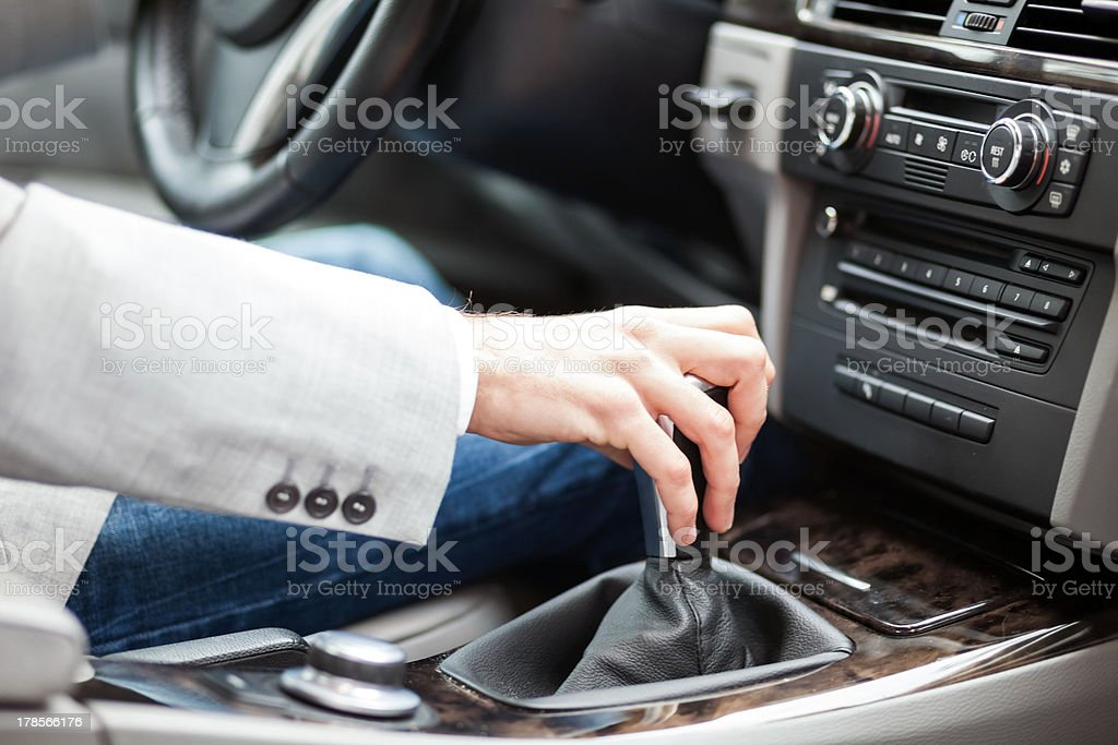 A man in jeans driving stick in a luxurious car stock photo