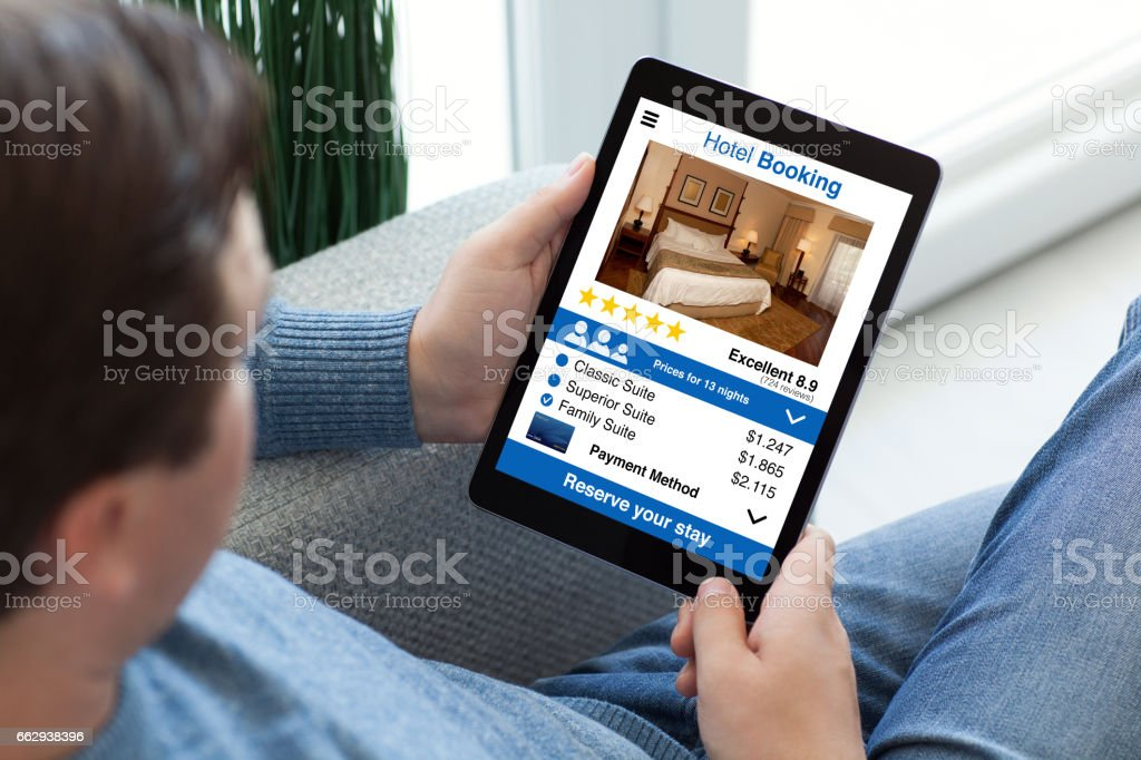 man in jeans holding tablet computer with app hotel booking stock photo