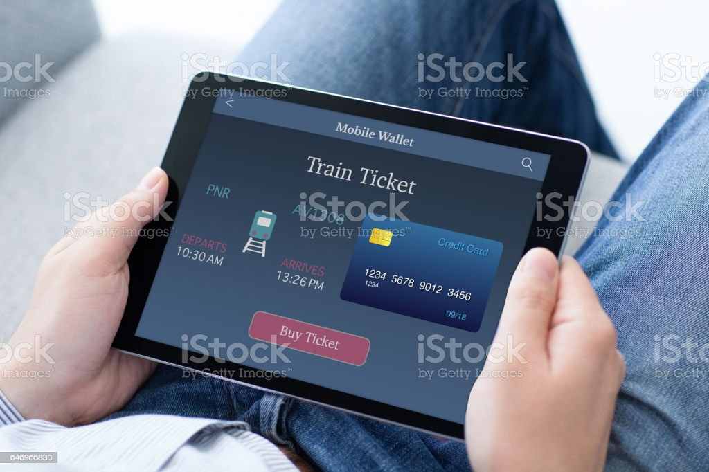 man in jeans holding tablet computer with online train ticket stock photo