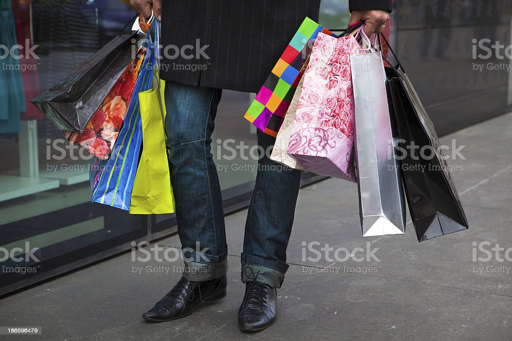 Man in jeans holds many brightly colored shopping bags royalty-free stock photo