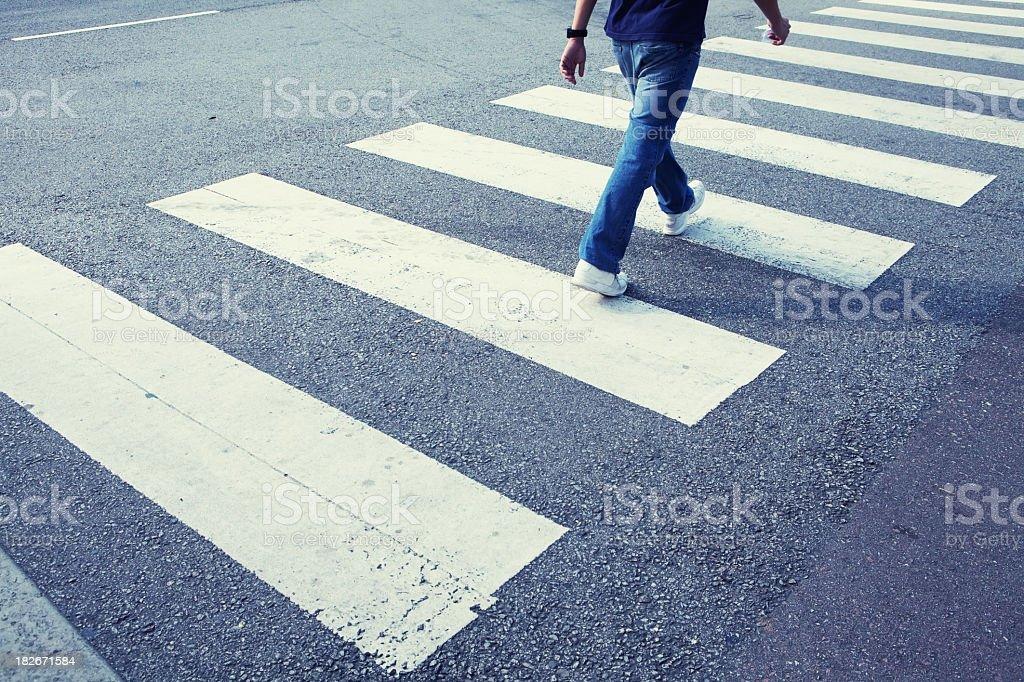 Man in jeans walking across a zebra crossing stock photo