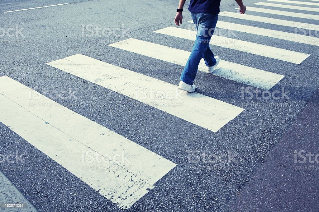 Man in jeans walking across a zebra crossing stock photo
