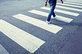 Man in jeans walking across a zebra crossing