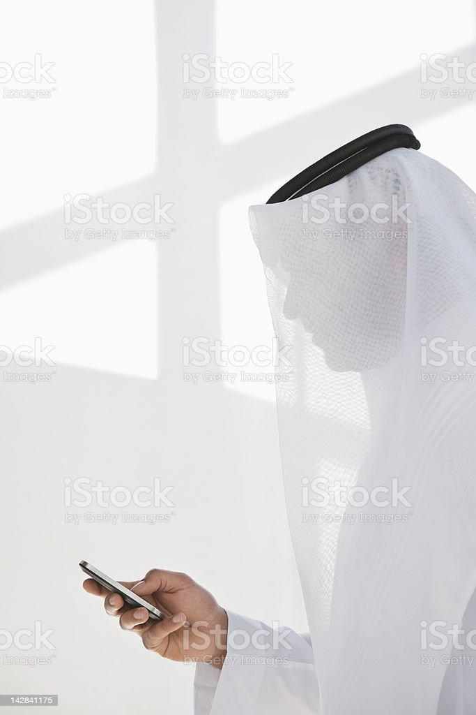 Man in kaffiyeh text messaging royalty-free stock photo
