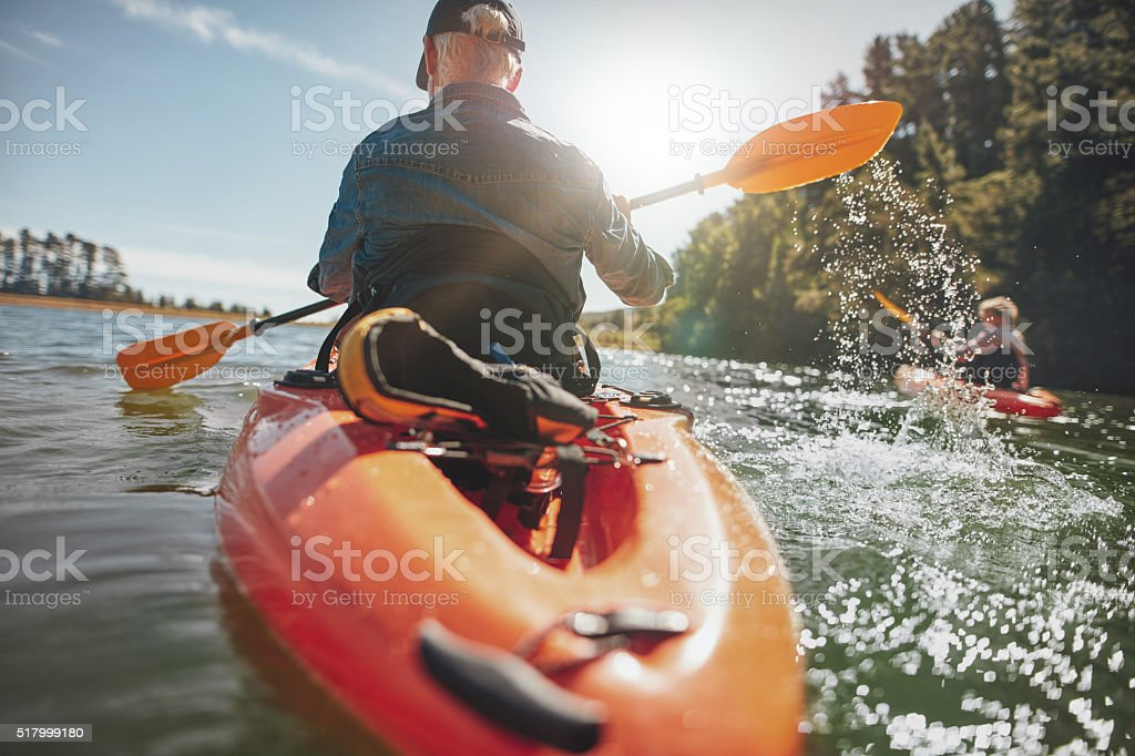 Man in kayak paddling on lake stock photo