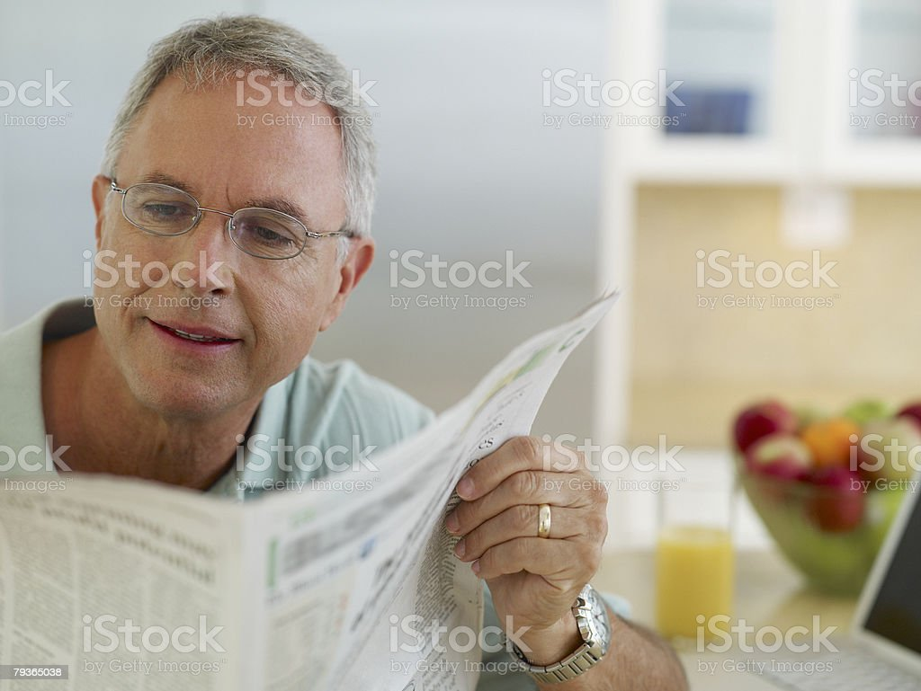 Man in kitchen reading newspaper royalty-free stock photo