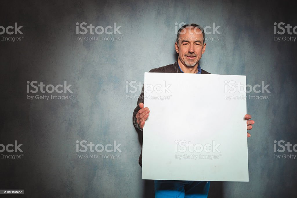 man in leather jacket holding blank board stock photo