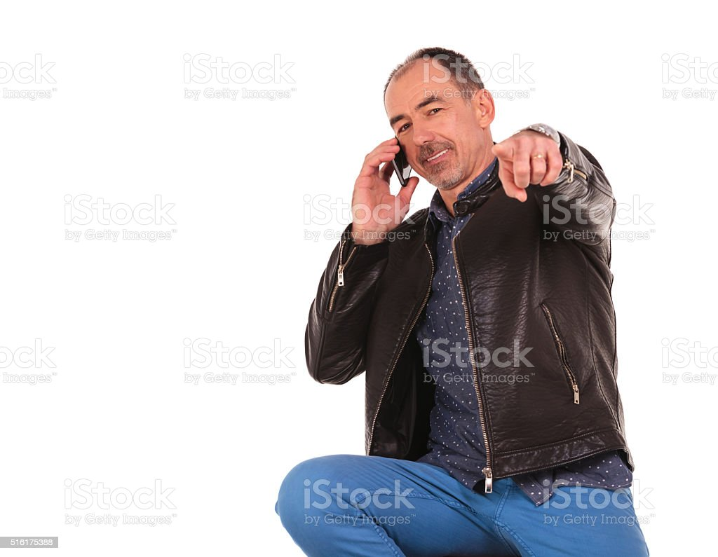 man in leather jacket pointing at the camera stock photo
