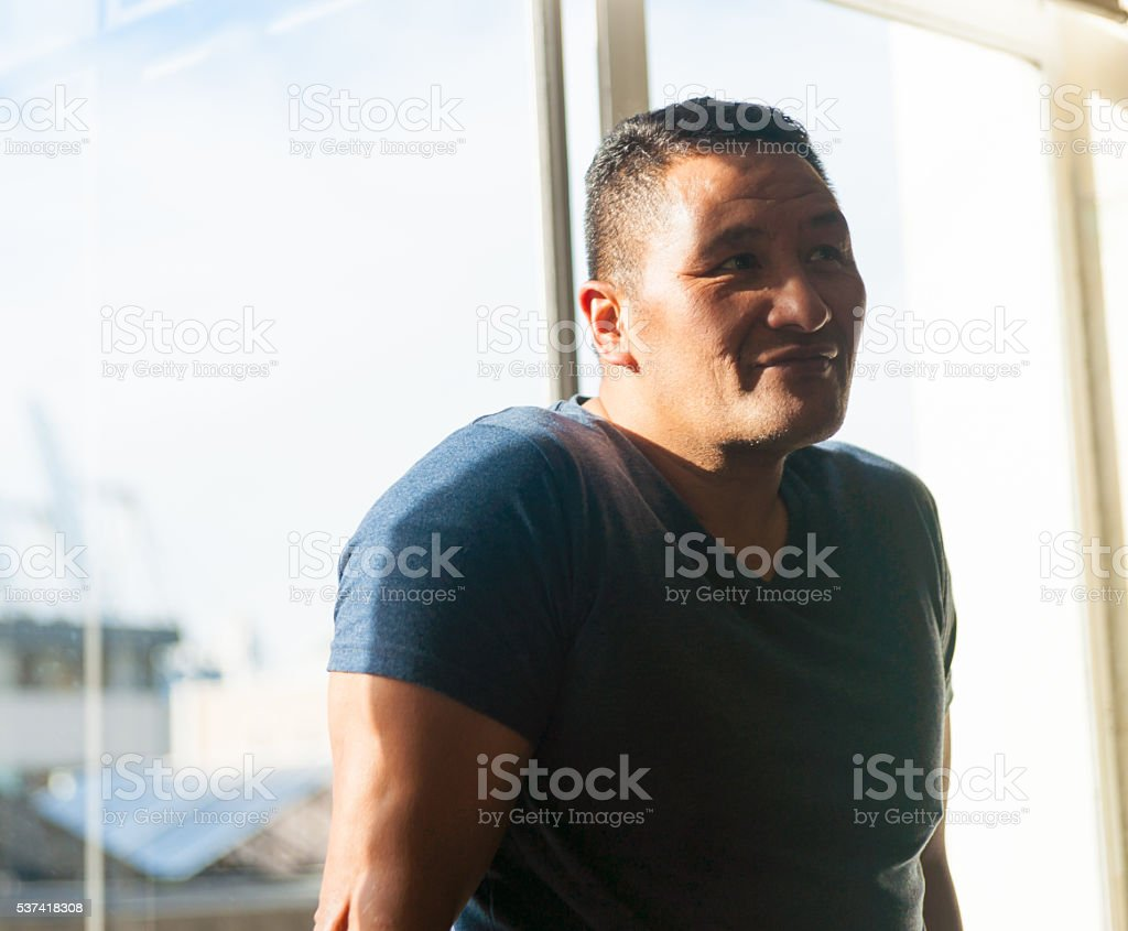 Man in light from side through window stock photo