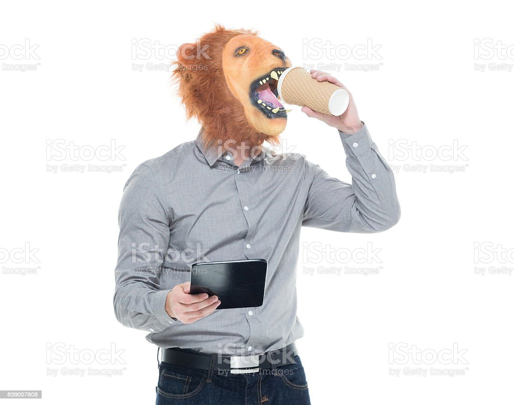 Man in lion costume and drinking coffee stock photo