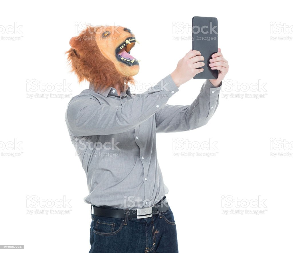 Man in lion costume and taking a selfie stock photo