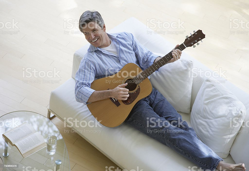 Man in living room playing acoustic guitar royalty-free stock photo