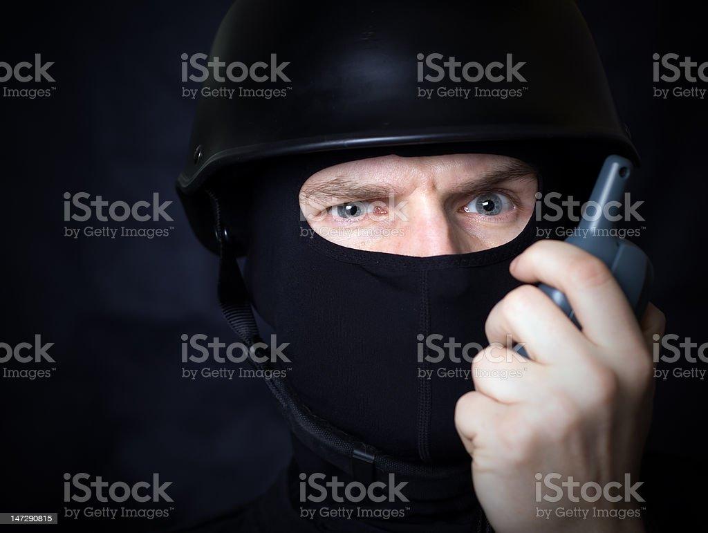 Man in mask talking on walkie-talkie radio royalty-free stock photo