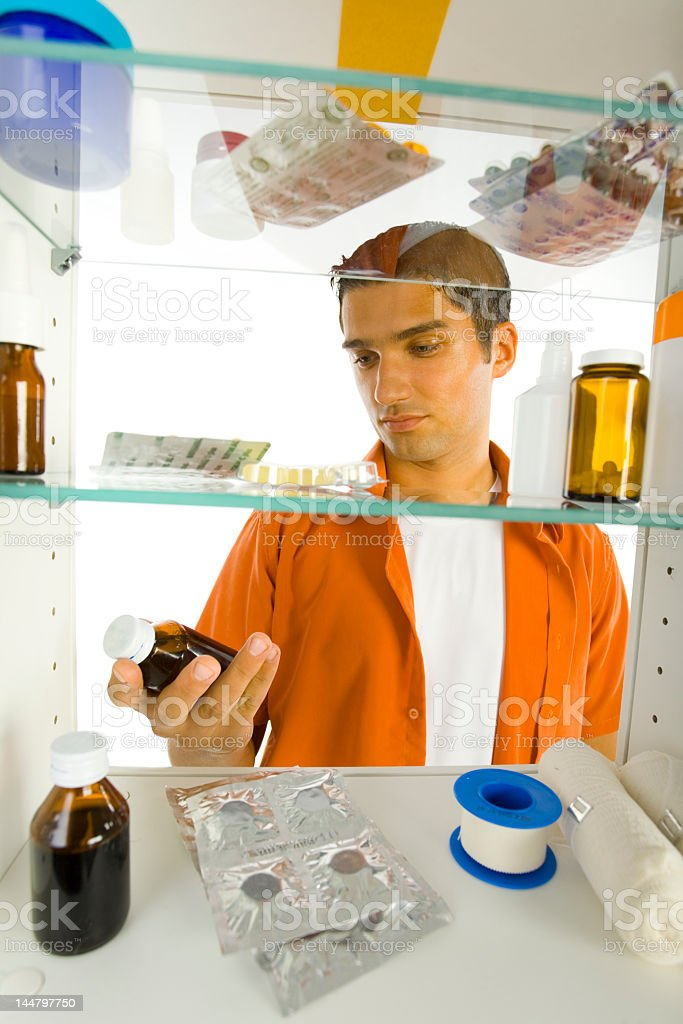 Man in medicine cabinet observing an unknown container stock photo