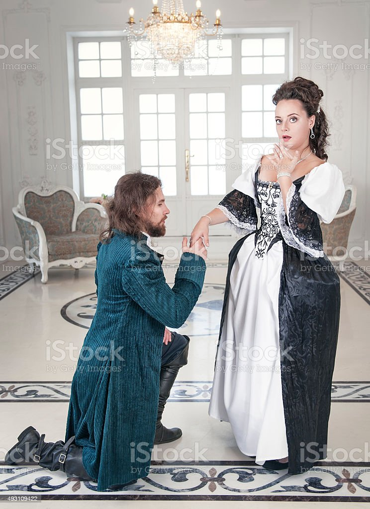 Man in medieval costume standing on the knee before woman stock photo
