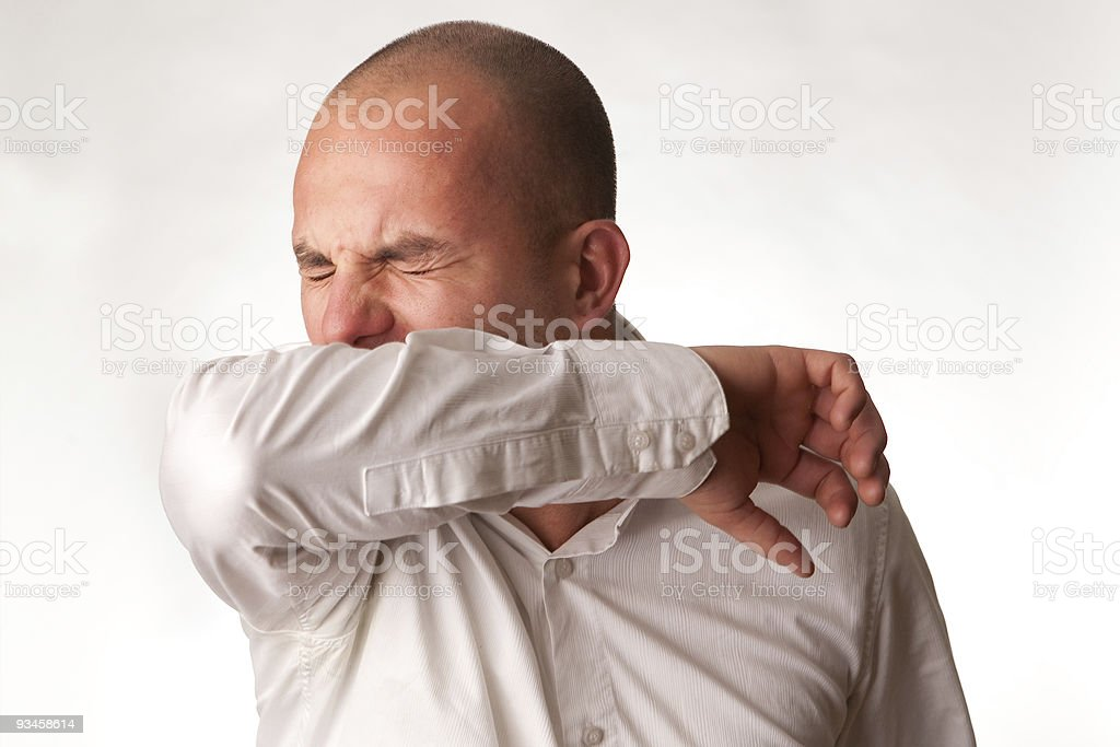 Man in mid cough demonstrating proper hygienic procedure stock photo